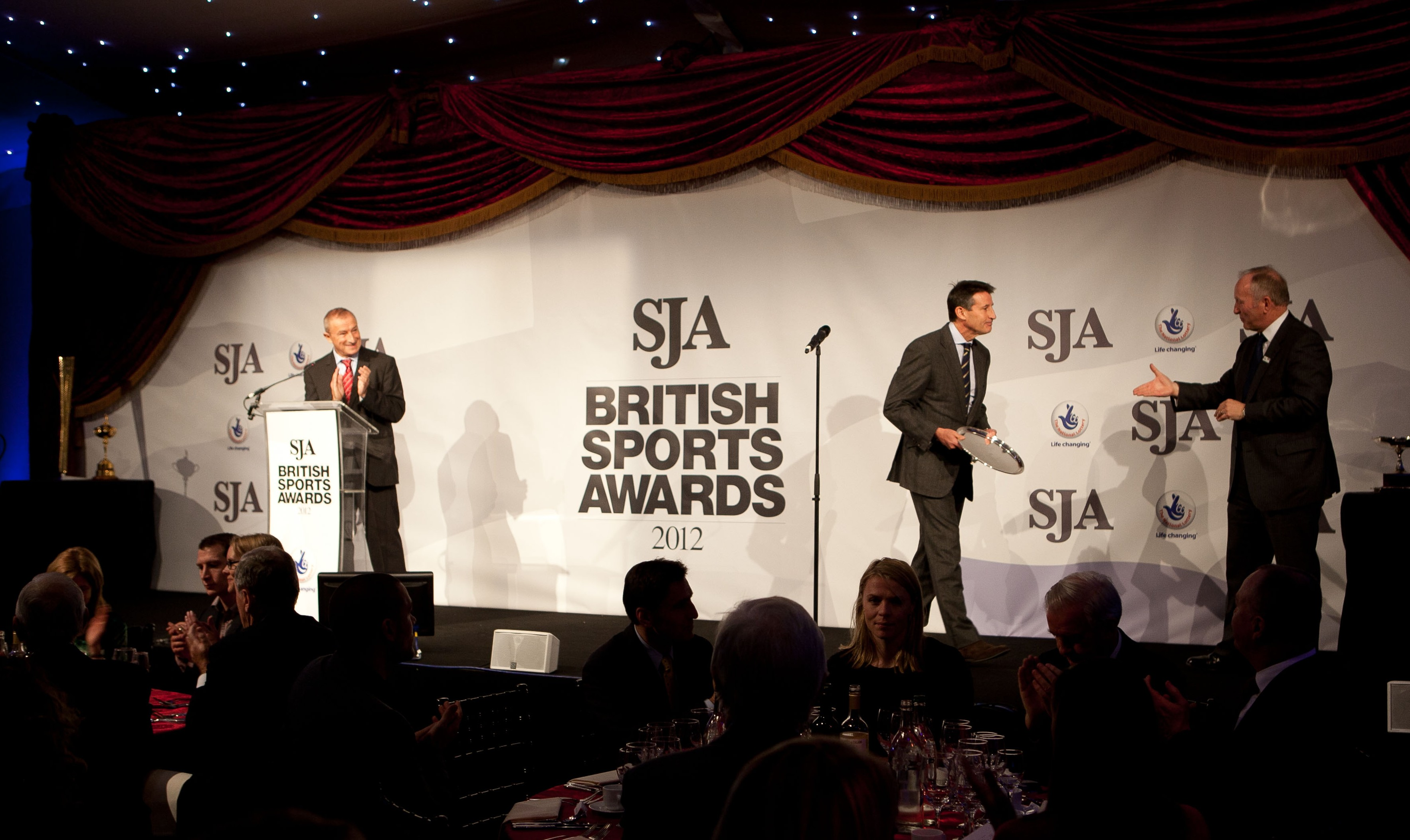Watched over by Jim Rosenthal, Sebastian Coe, the chairman of LOCOG, collects the JL Manning Award for services to sport from SJA vice chairman David Walker