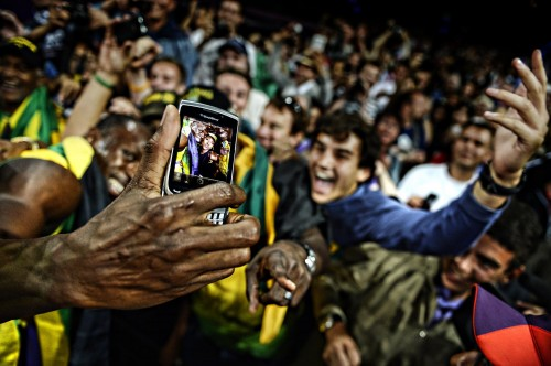 "One of the images that helped to win Adrian Dennis the title of Sports Photographer of the Year: Usain Bolt celebrates with fans by taking a ""Selfie"" with their mobile phone right after setting a world record with his Jamaican team in the 4x100m relay at the London Olympics"