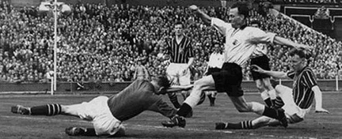 Moment of truth: Trautmann dives at the feet of in the fateful moment towards the end of the 1956 FA Cup final