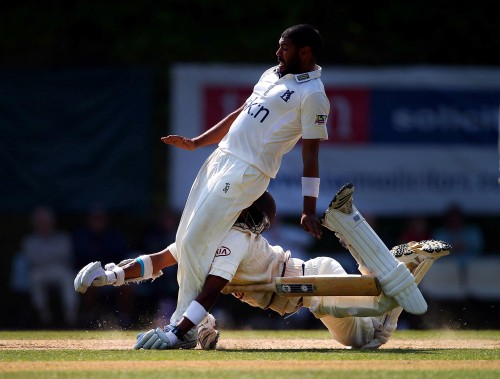 Arun Harinath of Surrey collides head first with Jeetan Patel of Warwickshire during day three of the LV County Championship Division One match between Surrey and Warwickshire at Guildford Cricket Club on June 07, 2013 in Guildford, England.  Photo by Clive Rose/Getty Images