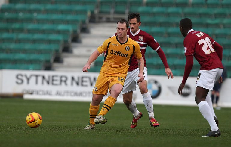 NEWPORT, WALES - JANUARY 04:  Mike Flynn of Newport County AFC plays the ball watched by Darren Carter and David Moyo of Northampton Town during the Sky Bet League Two match between Newport County and Northampton Town at Rodney Parade on January 4, 2014 in Newport, Wales.  (Photo by Pete Norton/Getty Images)